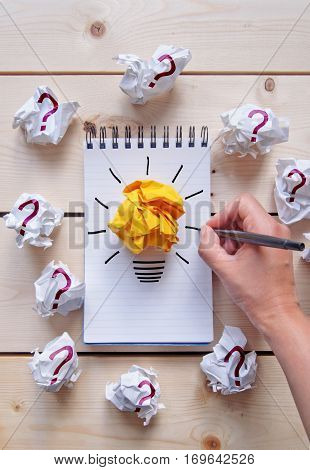 Drawing of a light bulb on a notepad with bright orange paper surrounded by crumpled pieces of paper with question marks