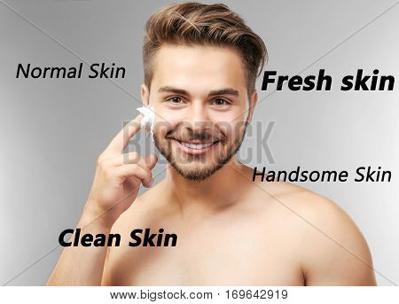 Skin care concept. Young man applying shaving foam, gray background