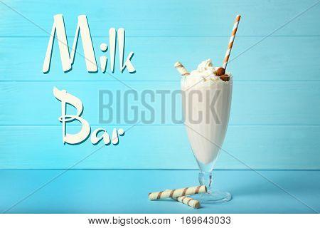 Glass of tasty milk shake on table. Text MILK BAR on background
