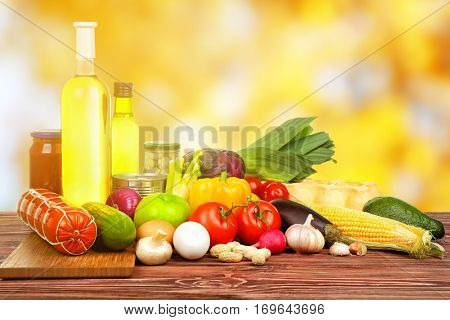 Various foodstuff on wooden table against blurred background