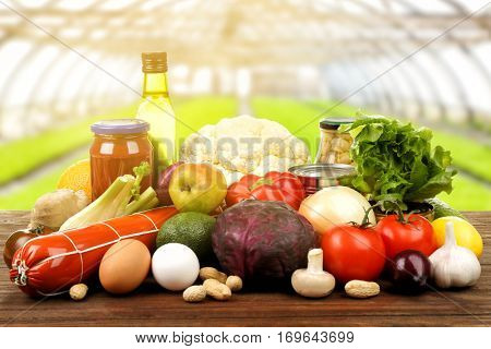 Various foodstuff on wooden table against greenhouse background