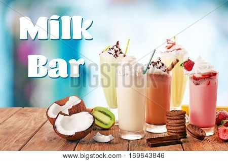 Different milk shakes on wooden table. Text MILK BAR on background