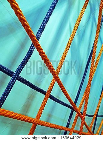 Crisscross tighted orange and blue fiber ropes