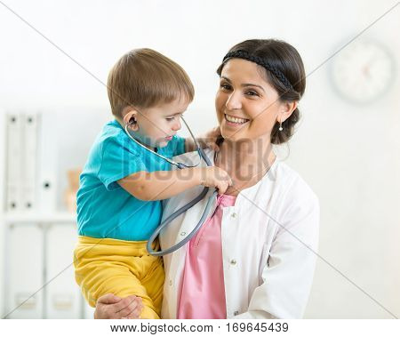 female pediatrician holding in her arms kid boy patient in office