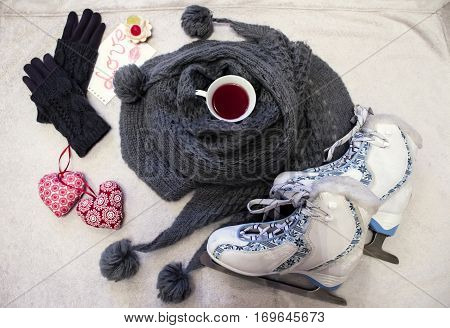 White-blue figure skates warm gray skarf with pompons cup of tea knitted gloves and cute textile hearts