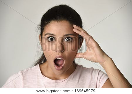 head portrait of young beautiful Spanish surprised woman amazed in shock and surprise with mouth big opened isolated grey background in astonished wow face expression