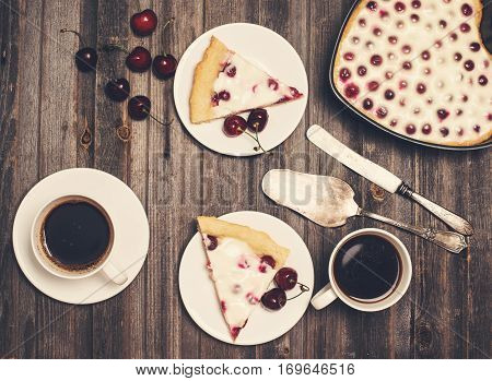 Retro styled valentine day background. Homemade cherry pie heart shape silverware and two cups of coffee with fresh cherries on wooden rustic background. Selective focus.