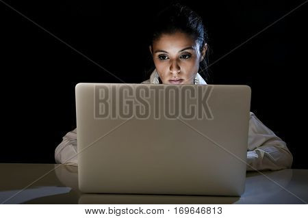 young business woman or student girl working in darkness on laptop computer late at night looking concentrated and tired in long hour of work concept isolated on black background