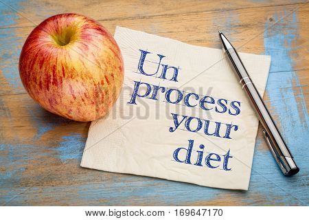 Unprocess your diet - healthy eating concept - handwriting on a napkin with apple