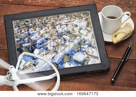 real estate aerial photography concept - reviewing  pictures of residential street in winter scenery on a tablet with a drone and coffee, screen image copyright by the photographer