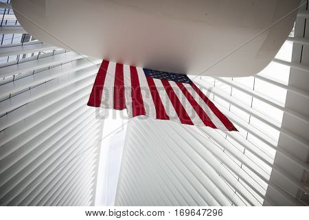 NEW YORK - SEPT 11 2016: The American Flag hanging in the World Trade Center transit hub known as the Oculus, with the Freedom Tower seen through the narrow opening in the ceiling.