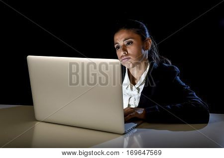 young mexican business woman or student girl working in darkness on laptop computer late at night looking stressed bored and tired in long hours of work concept isolated on black background