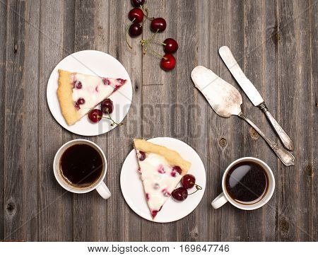 Cherry pie. Slice of homemade cherry pie and two cups of coffee with fresh cherries on wooden rustic background. Top view. Vintage background.
