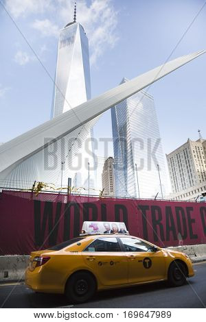 NEW YORK - SEPT 11 2016: A yellow NYC Taxi cab drives by the red World Trade Center sign on the fence along Church St at the construction site for Tower Two and new WTC complex.