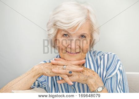 Senior woman smiling at camera with hands under chin