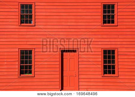 Four windows and door on red home