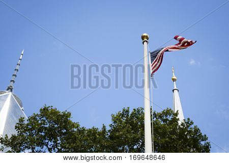 NEW YORK - SEPT 11 2016: Low angle view of the American Flag waving in the wind seen between the antenna on top of the Freedom Tower and steeple of St Pauls Chapel in Lower Manhattan.