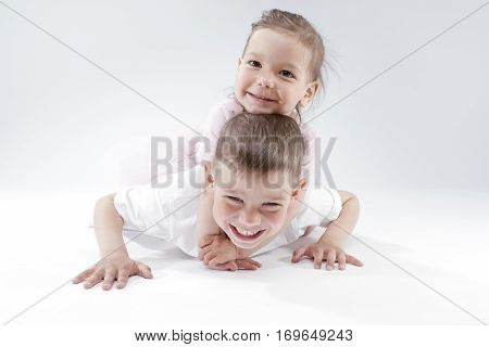Family Ideas and Concepts. Portrait of Happy and Smiling Brother and Sister Playing Together Underneath. Posing Against White. Horizontal Image