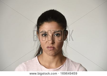 young beautiful arrogant and moody latina woman showing negative feeling and contempt facial expression isolated on grey background looking cocky and defiant