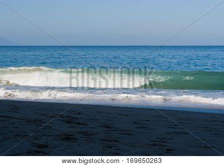 A big wave is crashing thunderously on the beach