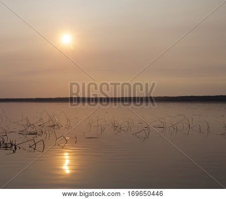 Dore Lake is Saskatchewan with the colorful sun overhead from fires in Alberta