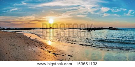 Tropical colorful dramatic sunset with cloudy sky. Beautiful seascape with sea and rock in Nang Thong Beach, Andaman Sea, Khao Lak, Thailand. Bright afterglow. Nature composition.