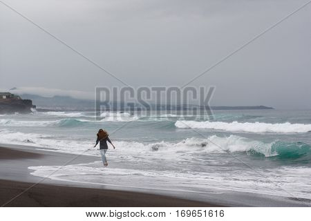 girl run ocean atlantic volcanic beach nature Portugal Azores island waves landscape