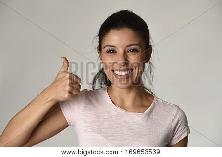portrait of young beautiful and happy Latin woman with big toothy smile excited and cheerful in charming face expression giving hand ok sign isolated clear grey in female happiness emotion