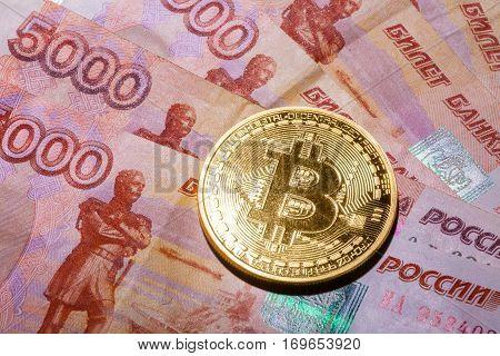One Bitcoin on Russian banknotes. Closeup, macro shot