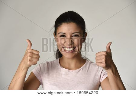 portrait of young beautiful and happy Latin woman with big toothy smile excited and cheerful in charming face expression giving thumb up sign isolated clear grey in female happiness emotion