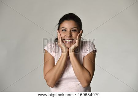 portrait of young beautiful and happy Latin woman holding face with hands with big toothy smile excited and cheerful facial expression isolated clear grey background in female happiness emotion