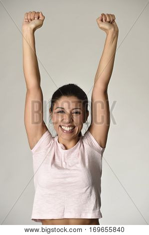 portrait of young beautiful and happy Latin woman with big toothy smile excited and cheerful in charming face expression rising fist isolated clear grey in female victory and success concept