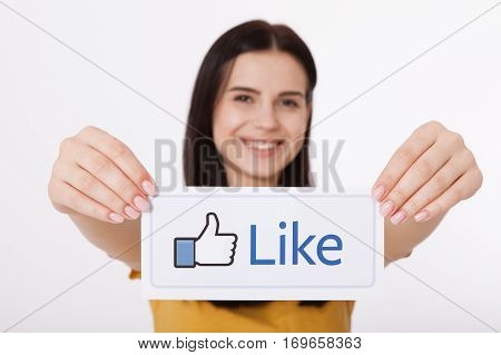 KIEV, UKRAINE - August 22, 2016: Woman hands holding facebook thumbs up sign printed on paper on white background. Facebook is a well-known social networking service.
