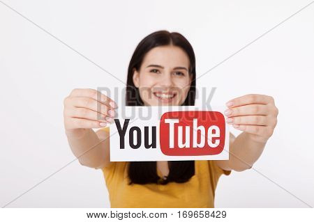 KIEV, UKRAINE - August 22, 2016: Woman hands holding paper with YouTube logotype printed on paper. YouTube is a video-sharing website headquartered in San Bruno, California.