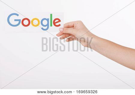 Kiev, Ukraine - August 22, 2016: Woman hands holding colorful Google logotype printed on paper on grey background.Google is USA multinational corporation.