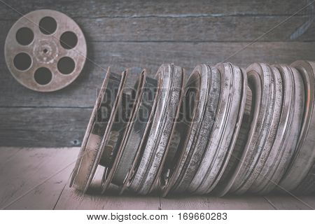 Stack of reels of old movies is on a wooden shelf