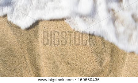 Foamy waves washing over the beach sand