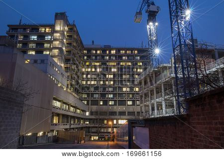 The back side of a central hospital in London with the lights on at dusk. Construction site on the right for residential homes.