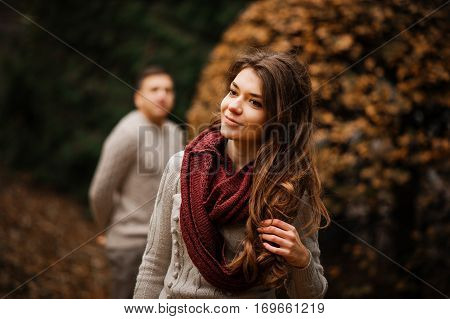 Yong Couple Wearing On Tied Warm Sweaters Hugging In Love At City In Autumn Background Yellow Bushes