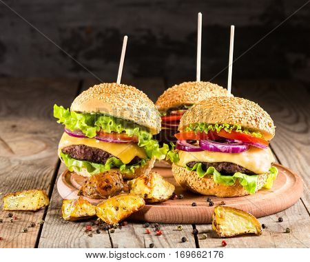 burgers with beef and fried potatoes on wooden table