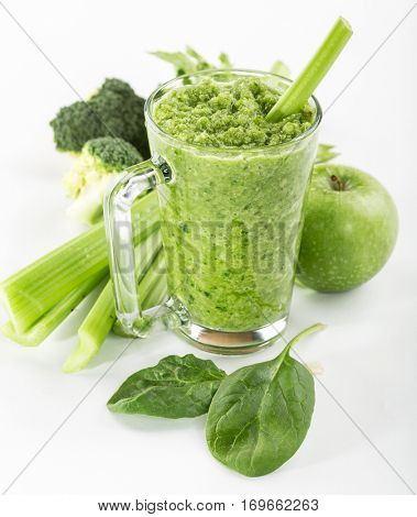 healthy green smoothie in a glass of spinach, celery and apple on a white background