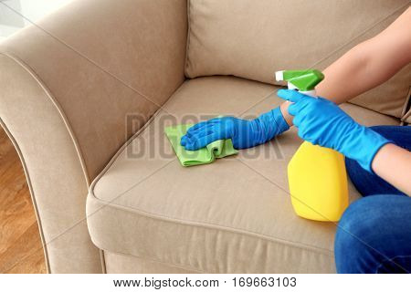 Young woman cleaning sofa with duster, closeup