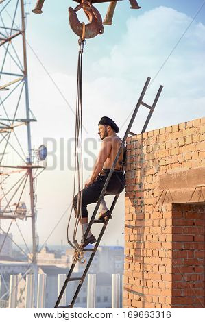 Athletic builder with bare torso sitting on ladder on high. Man leaning on brick wall and looking away. Extreme building in hot weather. Crane and TV tower on background.