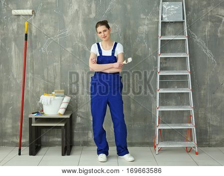 Young female decorator with special tools and ladder near grunge wall