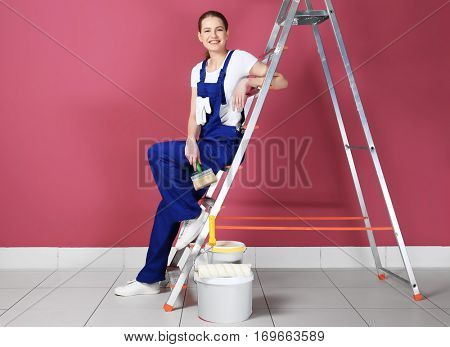 Beautiful young decorator sitting on ladder in empty room