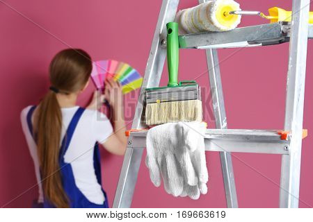 Ladder with painting tools and young decorator on background