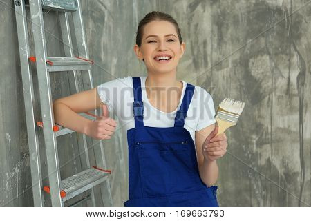 Young female decorator near ladder in empty room