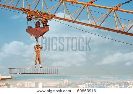 Muscular builder with bare torso standing on iron construction on high and holding by ropes. Man wearing hat and work wear looking at camera. Blue sky with clouds on background.