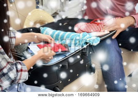 Winter vacation concept. Snowy effect on background. Couple packing stuff into suitcase at home