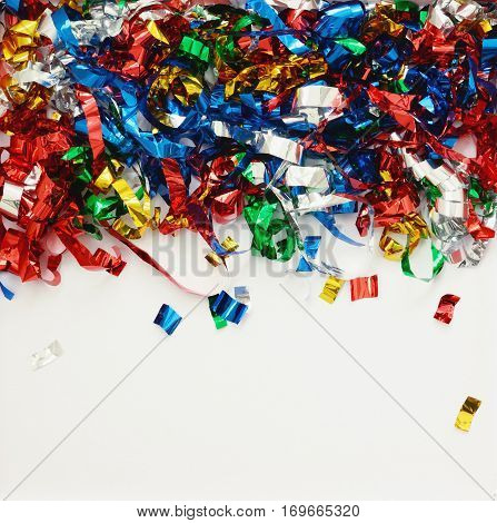Background with scattered colorful confetti on white paper